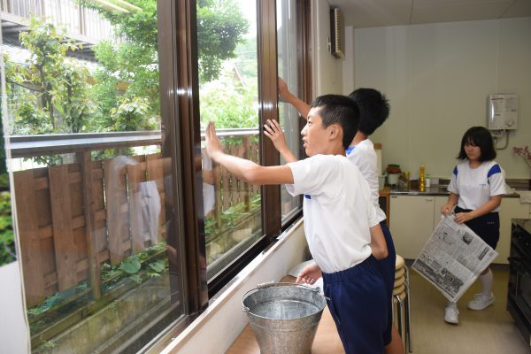 調理室の窓ガラスを拭く釜中ボランティア隊