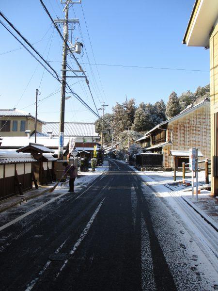 雪を竹ぼうきで取り除く丸森邸職員